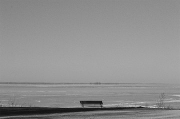 Empty park bench overlooking frozen river